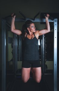 women performing a pull-up at the gym