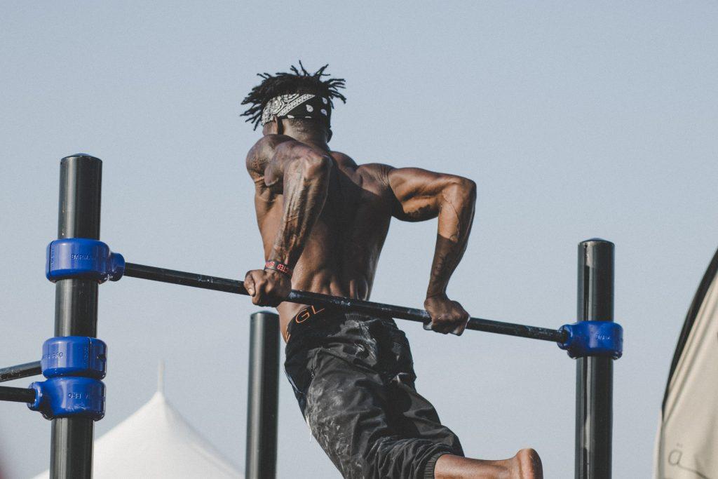 man performing reverse dip exercise on high bar